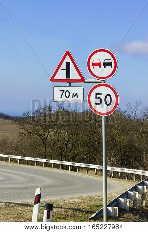 Road signs speed limits and ban on overtaking at a sharp turn of the highway