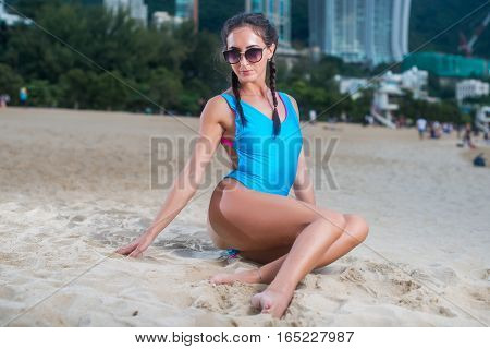 Portrait of beautiful young female model in swimwear sitting on the beach at tropical resort.