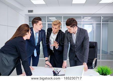 Team of business people work at a desk in modern office.
