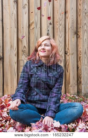Young woman sitting against fence in fallen red autumn leaves smiling