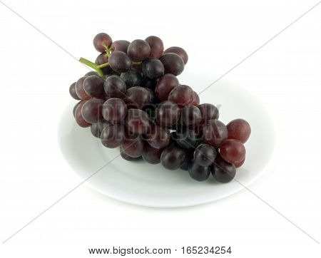 Red wine grape branch with tasty berries lays on plated isolated over white close up