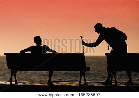 Silhouette of young mens on the bench as photos at sunset on the sea