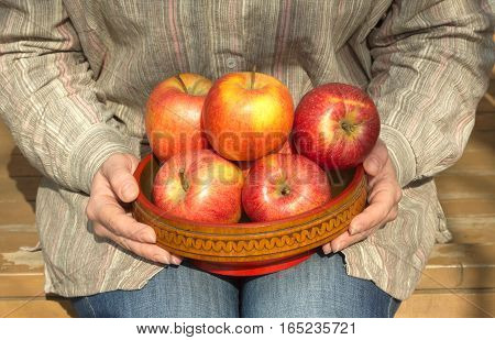 Woman in blue jeans and gray stripe shirt sits on porch of wooden  house and holds wooden bowl with ripe appetizing apples. Close up photo