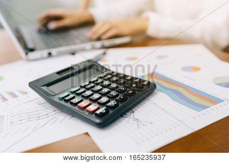 Close up shot of calculator with businesswoman working in background