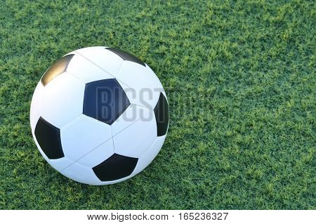 Football or soccer ball on the green grass with copy space for text,outdoor activities.