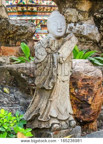 Stone statue in the ancient Wat Arun Temple or The Temple of Dawn. Bangkok, Thailand