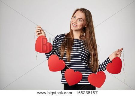 Beautiful smiling woman holding garland of five red paper hearts shape - blank copy space for letters or text, looking to the side