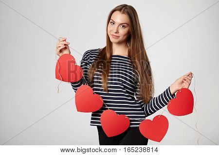 Beautiful smiling woman holding garland of five red paper hearts shape - blank copy space for letters or text, looking at camera