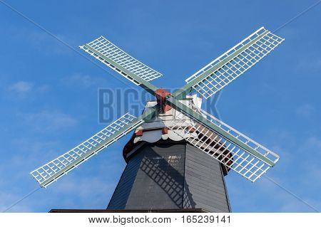 image of wooden windmill against the blue sky