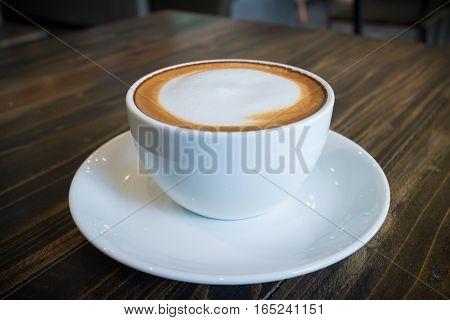 hot coffee mocha with foam milk art in vintage cafe