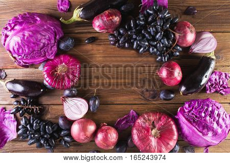 Purple fruits and vegetables. Blue onion purple cabbage eggplant grapes and plums on a wooden background.