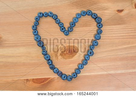 Blueberry berries in a heart shape on wooden background.