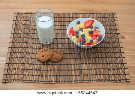 Healthy breakfast of fruit berries and oatmeal cookies with milk on a wooden background