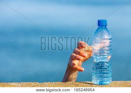Male hand taking away water plastic bottle outdoor on sea shore