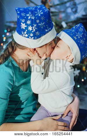 Mother kisses the child against the background of the Christmas tree