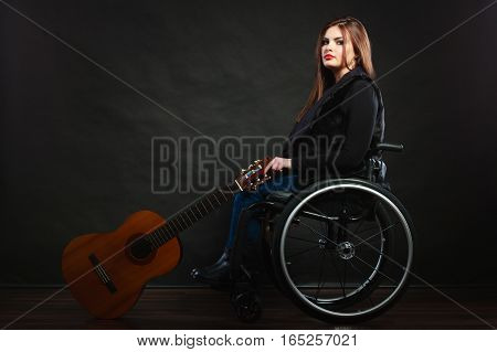 Sad disabled girl with guitar. Young female musican on wheelchair. Disability health passion hobby concept.