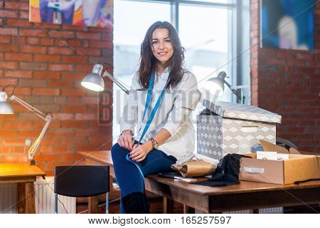 Pretty brunette female dressmaker sitting on table looking at camera surrounded by tailor s attributes in sewing workshop with loft interior.