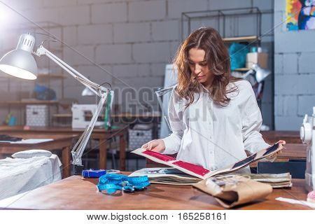 Young female dressmaker choosing material from catalogue in studio. Tailor looking through fabrics while standing in a sewing workshop.