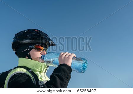 Traveller cyclist drinking water from a bottle while relaxing.