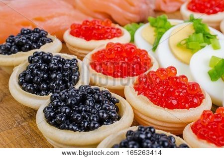 Tartlets with caviar salted salmon and eggs. On a wooden background.