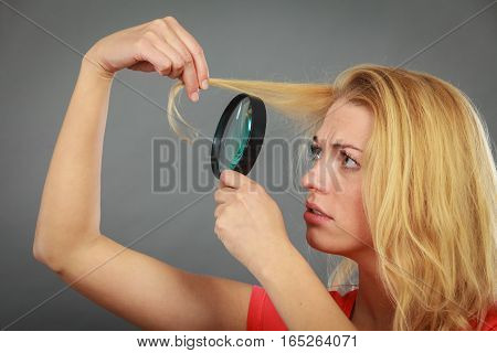 Haircare health problem concept. Unhappy woman looking at ends of her blonde hair through magnifying glass