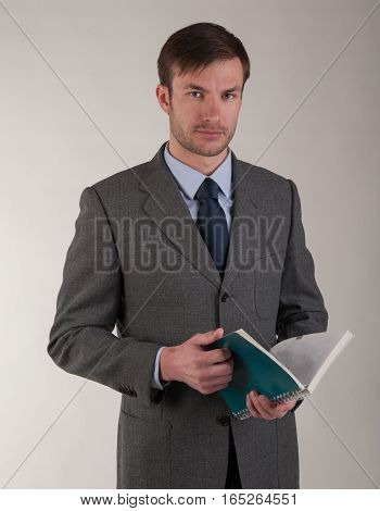 Portrait of a serious businessman in a suit with an open book