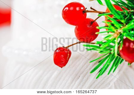 Winter or christmas decorative macro with evergreen twigs, red berries and pearl beads on white texlile background