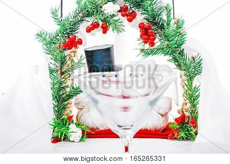 Wedding ceremony of toy yarn snowmen couple under winter decorated arch. View through the wine glass. Concept of winter weddings