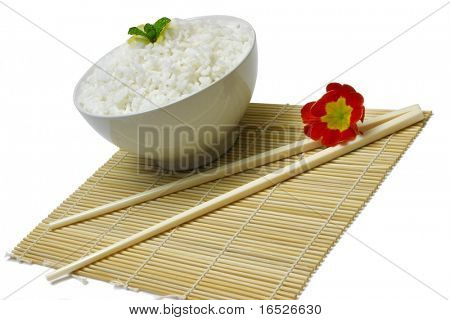 Bowl of cooked white rice with chopsticks on sushi mat, isolated on white
