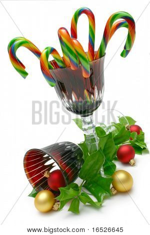 Christmas theme goblets, holly, baubles and candy canes on white background