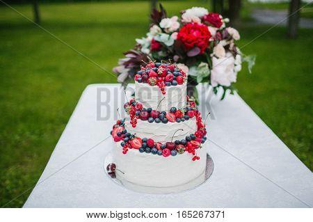 Wedding cake with berries white. Sweet dessert.