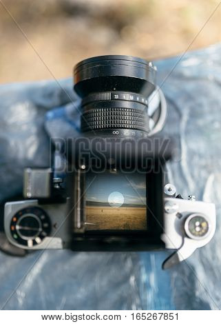 View through the prism of the old Soviet medium format camera. Frame - The boy on a beach with a kite. Viewfinder screen on medium format camera with hand holding.