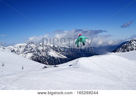 Snowboarder Jumping In Snow Park At Winter Mountain On Nice Sunny Day