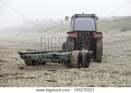 A red beach tractor with green trailer returning from launching a fishing boat on a misty morning