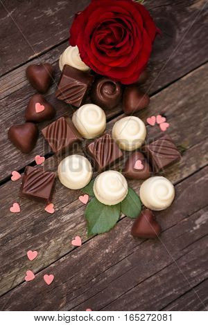 Various chocolate pralines and red roses background