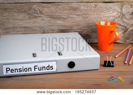 Pension Funds. Folder, Coffee Mug, colored pencils on wooden office desk.