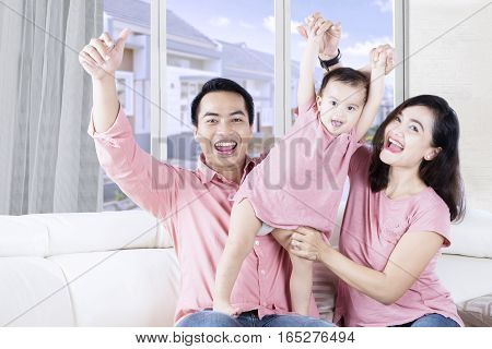 Picture of happy Asian little girl playing with her parents in the living room while laughing and raising hands together on the sofa