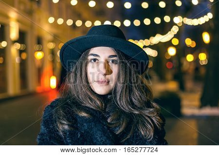 Close-up portrait of fashion and vogue model woman with dark hat on looking away and posing for photographer