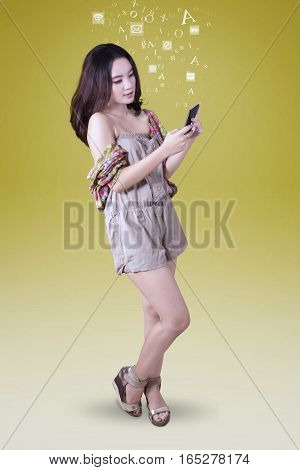 Full length of beautiful teenage sending message by using her smartphone