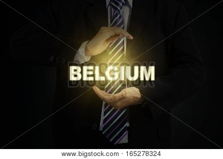Close up of two arm businessman holding a bright Belgium word