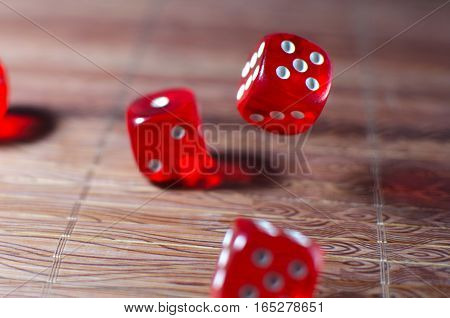 Red dice cubes with white points lying on the wicker wooden canvas background. Shallow depth of field.
