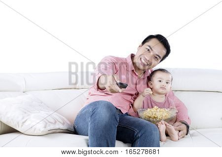 Portrait of a young Asian man and her daughter watching TV while eating popcorn on the sofa