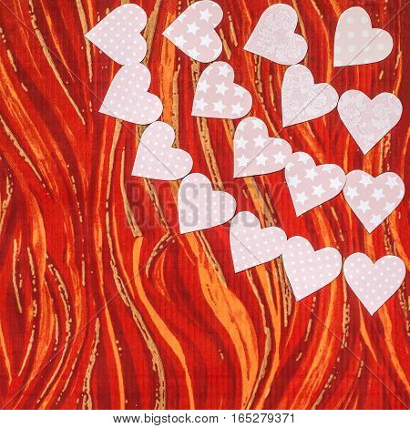 Garlands of tender pink hearts carved by hand from paper with various ornaments on a red background. Festive background to Valentines Day with empty space for text