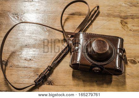 vintage photo camera leather case over wood background