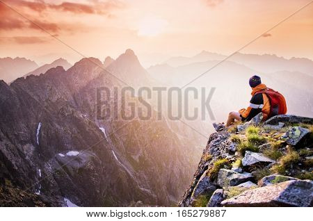 Young tourist hiker with backpack siting on the top of the hill mountains and looking at beautiful summer sunset