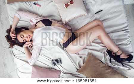 Top view photo of amazing woman with red lips, curly hairstyle, glowing skin, perfect legs posing at bedroom, sexually bites finger on her mouth. Lady lying on stomach on white bed, sexy tan.