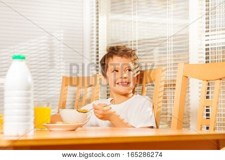 Smiling kid boy sitting at breakfast holding spoon with corn flakes in sunny morning