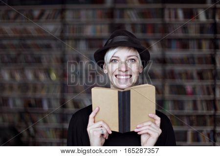 Portrait of woman in black hat with opened book smiling in a library blonde hair. Hipster student girl