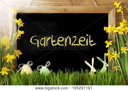 Blackboard With German Text Gartenzeit Means Garden Time. Sunny Spring Flowers Nacissus Or Daffodil With Grass, Easter Egg And Bunny. Rustic Aged Wooden Background.