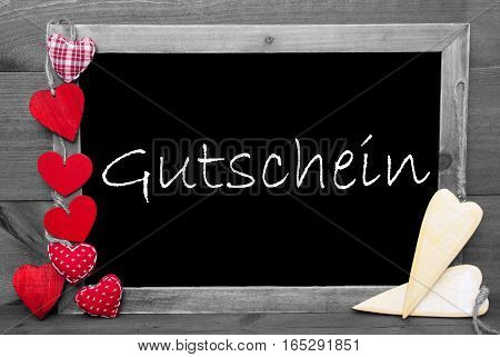 Chalkboard With German Text Gutschein Means Voucher. Red Hearts. Wooden Background With Vintage, Rustic Or Retro Style. Black And White Image With Colored Hot Spots.